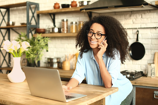 Female African-American freelancer talking by phone while working on laptop in kitchen