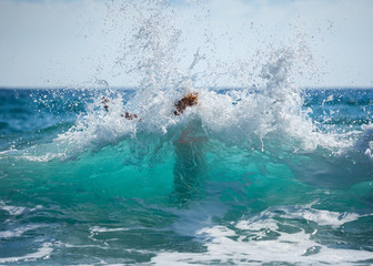 Young woman in bikini unexpected flooded with big wave