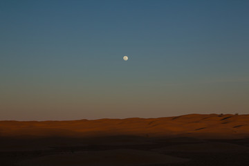 Full moon over the sand dunes during an off road trip through the northern Sahara in Tunisia  south of the city of Dousz