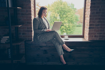 Close up side profile photo busy she her business lady concentrated hot beverage look hold notebook check e-mail letters sit window sill office wear specs high-heels formalwear checkered plaid suit