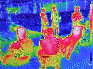 Infrared thermovision image showing when People sit at the table in the summer