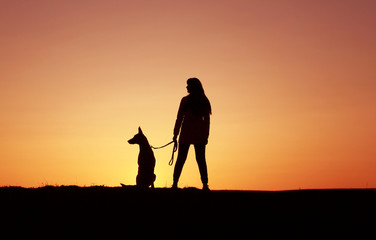 Silhouettes at sunset, girl and dog against the backdrop of an incredible sunset, Belgian Shepherd dog Malinois