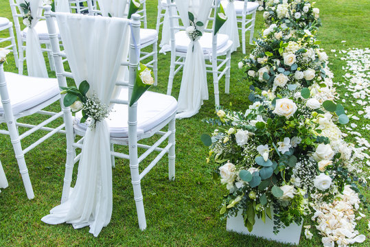 Chair decorated with flowers in Wedding ceremony.