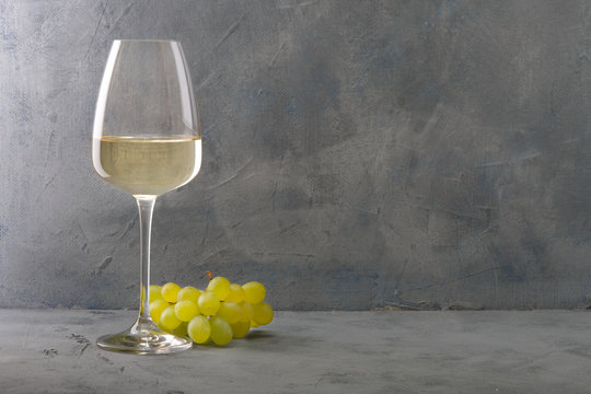 Glass of white wine on vintage wooden table