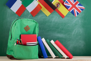backpack, flags of Spain, France, Great Britain and other countries, books and school supplies of the blackboard