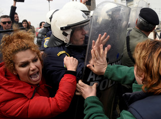 Migrants and refugees scuffle with riot police officers near the town of Diavata