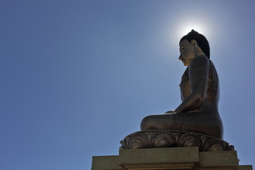 Buddha Dordenma statue silhouette on blue sky background with sun halo around its head in Thimphu, Bhutan