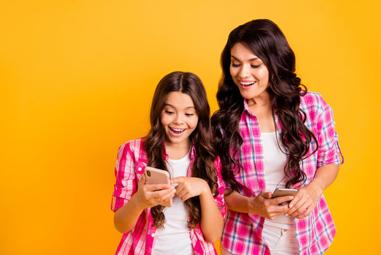 Close up photo beautiful mom small little daughter finger look what I have telephone smart phone yeah yes sms good news information wear casual pink plaid checkered shirts isolated yellow background
