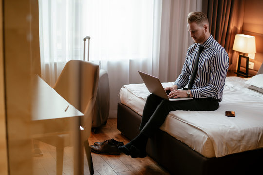 Man working on his laptop. Executive manager talking on the phone while working on his laptop. Businessman sitting on the bed working.