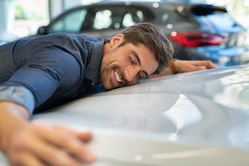 Young man hugging new car Fototapete