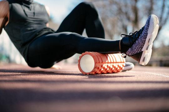Man foam rolling. Athlete stretches using foam roller.