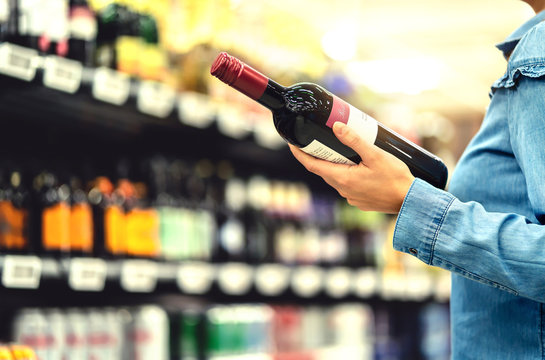 Alcohol shelf in liquor store or supermarket. Woman buying a bottle of red wine and looking at alcoholic drinks in shop. Happy female customer choosing merlot or sangiovese. Shopping spirits concept.