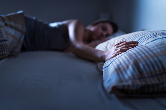 Single woman sleeping alone in bed at home. Lonely lady missing husband or boyfriend. Hand on pillow. Solitude, infidelity or heartbreak concept. Loneliness and sorrow after break up or divorce.