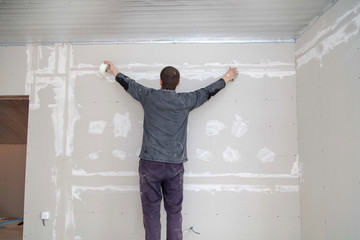 Worker aligns the walls with plaster. Repair in the house
