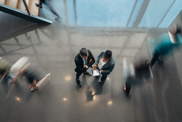 Two business people standing in the lobby of an office looking at a tablet while people are walking past in a blur Wall mural