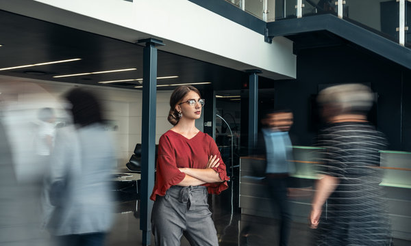 Beautiful young business woman standing in a busy lobby of an office with her arms crossed, looking ahead, with people walking past in a blur