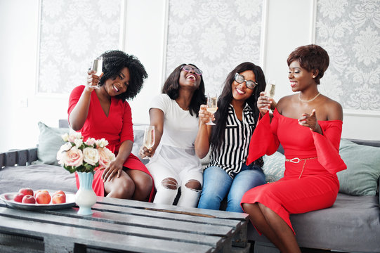 Group of partying african girls clinking glasses with sparkling wine champagne.