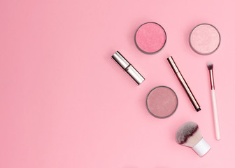 Flat lay composition with decorative makeup products on pastel pink background.