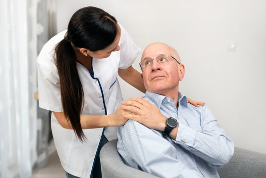 Smiling nurse and old senior man patient at home