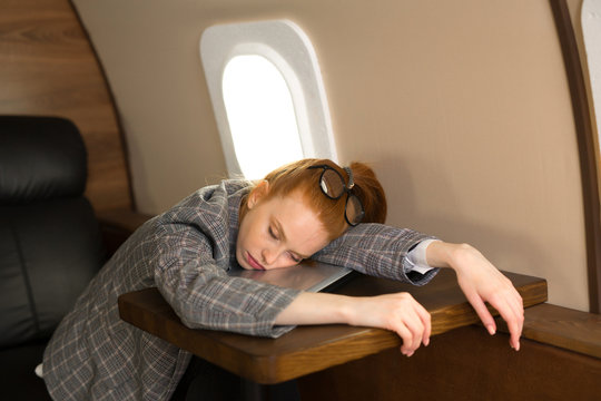 beautiful young girl with red hair is flying in a business class plane and sleeping on a laptop
