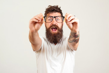 Excited bearded man touching the spectacles and keeping his mouth open against white background. Handsome smart guy with great idea. Surprised bearded young man.