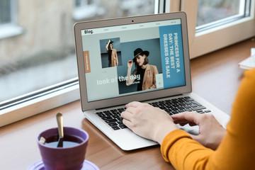 Female fashion blogger working on laptop near window