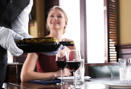 Waiter pouring wine in glasses for clients in restaurant
