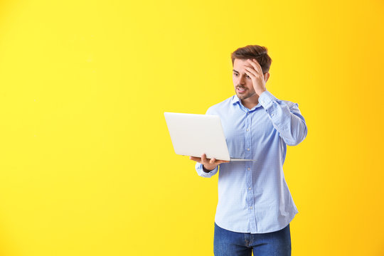 Shocked male programmer with laptop on color background
