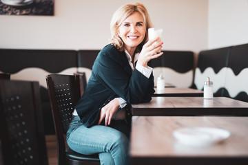 Fototapeta Attraktive,  ältere Frau sitzt im Cafe, hält einen Latte Macchiato in der Hand und lächelt freundlich in die Kamera  obraz
