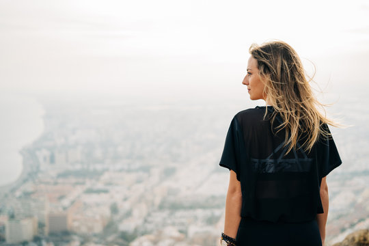 Young beautiful woman on top of the mountain looking at the city from above