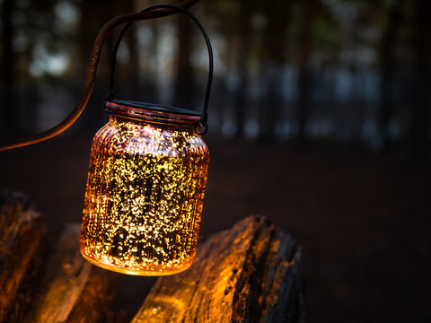Solar powered lantern hanging above firewood pile in forest. Glowing lantern in rustic outdoor camping area. Illuminated copper colored glass lantern with yellow color light.