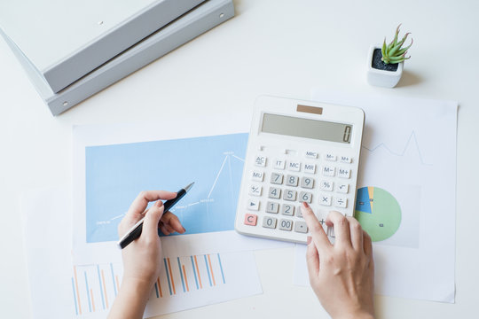 Businesswoman using a white calculator to calculate the value of business financial