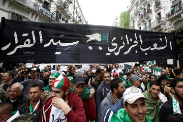 People march during a protest to push for the removal of the current political structure