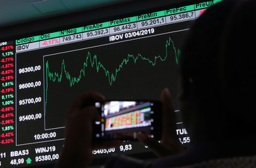 A woman takes a picture of an electronic board showing the recent fluctuations of market indices on the floor of Brazil's B3 Stock Exchange in Sao Paulo