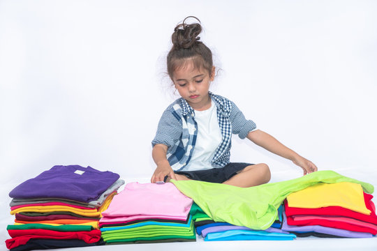a lovely boy holding green tee shirt behind colorful pile of tee shirts in white background.