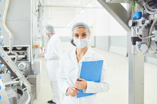 Technologist woman at food factory .