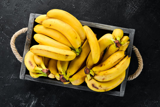 Fresh bananas in a wooden box. Top view. Free copy space.