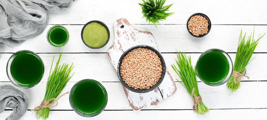 Healthy green wheat drink on a white background. Top view. Free space for your text. Wall mural