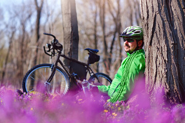 Smiling cyclist under the tree in the forest