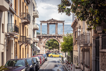 Fototapete - Street in Athens overlooking the ancient Hadrian's Gate or Arch of Hadrian, Greece. It is a landmark of Athens. View of historical district in the Athens city. Old architecture of the Athens center.