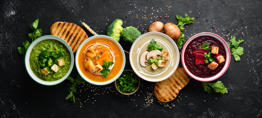 Assortment of colored vegetable cream soups. Dietary food. On a black stone background. Top view....