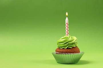 Delicious cupcake with a candle on a colored background with space to insert text. Festive background, birthday.