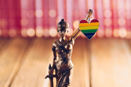 Statue of Temide - symbol of law and justice holding heart with lgbt colours