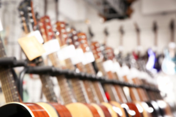 Row of different guitars in music store, blurred view