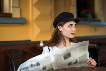 Young woman having a breakfast reading newspaper outdoors at the typical french cafe terrace in France. Playful girl with long hair posing outdoor. Wearing wool cap. Street fashion look. Cute teen