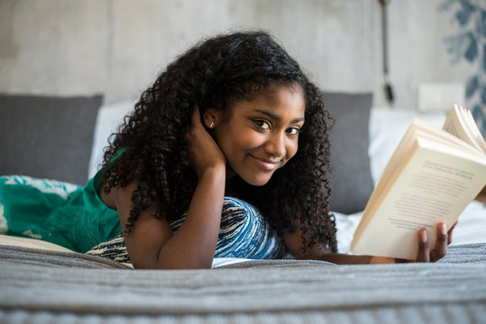 Beautiful happy black teenage girl on bed reading a book