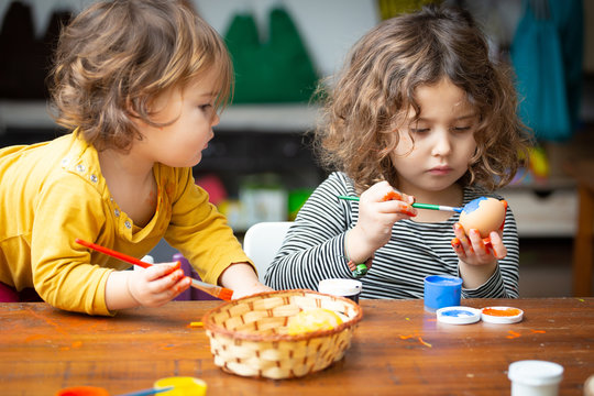 Two cute girls with brushes painting chicken eggs for Easter while sitting at wooden table together