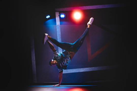 Modern ethnic man in denim and white sneakers showing contemporary dance in handstand position
