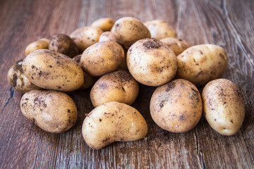Young raw uncooked potato on table