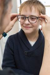 Cute young boy trying on glasses in an eyewear store